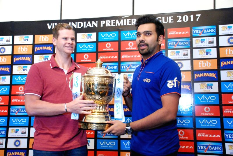 Mumbai Indians captain Rohit Sharma and Rising Pune Supergiant captain Steve Smith pose with the IPL trophy in Hyderabad on May 20, 2017. - Rohit Sharma