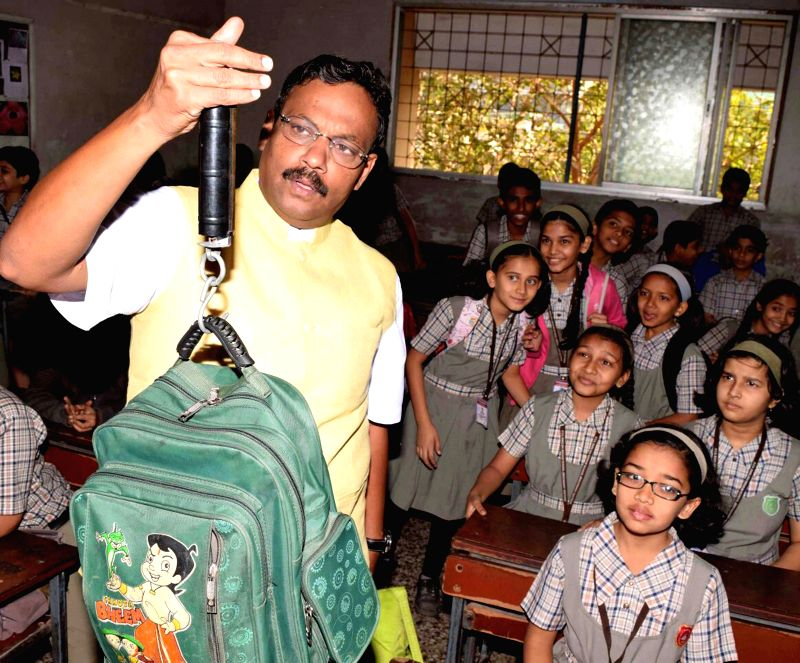 Maharashtra Education Minister Vinod Tawde weighs the school bags of students at a Vile Parle  School on Feb 13, 2015.