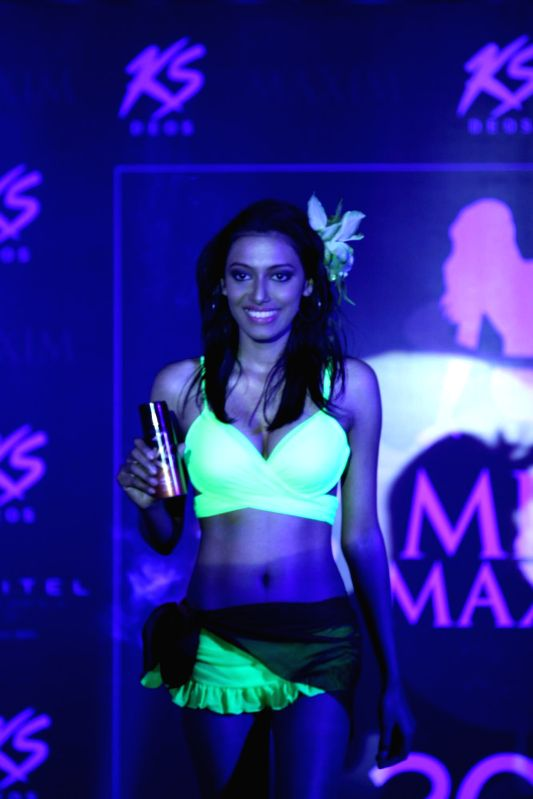 Model walks on the ramp during the grand finale of Kama Sutra Miss Maxim 2015, in Mumbai, on Dec 21, 2014.
