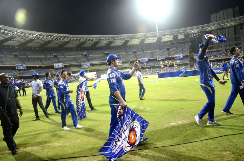 Mumbai Indians players celebrate the team's triumph in the eight edition of Indian Premier League at the Wankhede Stadium in Mumbai on May 25, 2015.