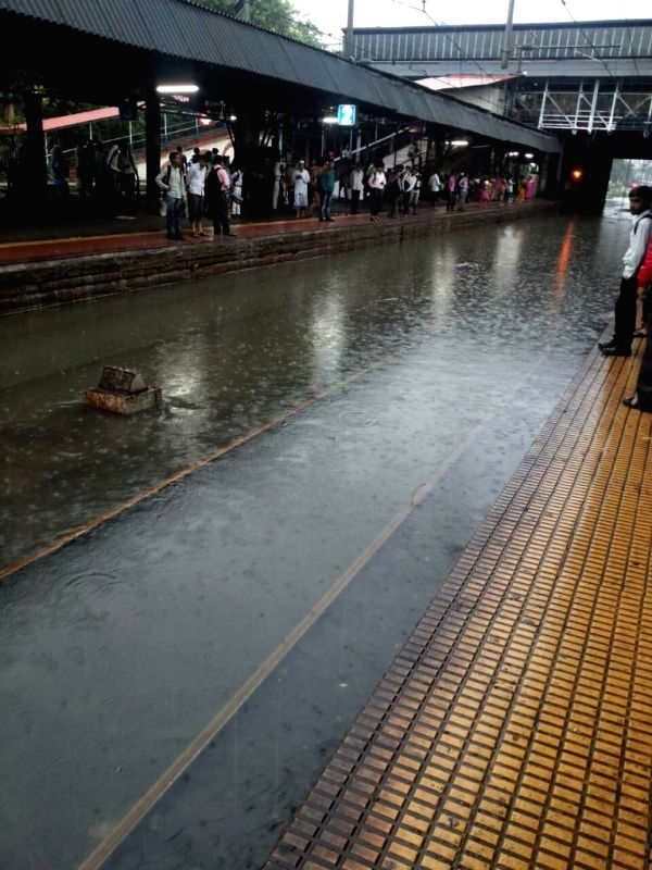 People wait for a trian on a submerged track as heavy rain hit train services in Mumbai on June 19, 2015.
