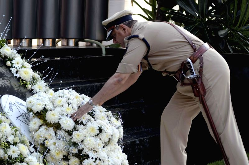 Mumbai Police Commissioner Rakesh Maria pays homage to those killed in the 26/11 attacks during a programme at Police Gymkhana in Mumbai on Nov.26, 2014.Ten heavily armed Pakistani terrorists had ...
