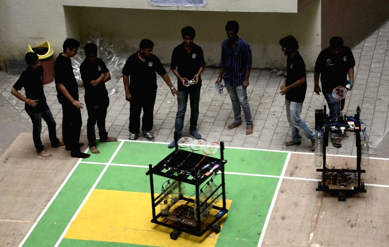 Robots controlled by students play badminton in Mumbai on March 24, 2015.