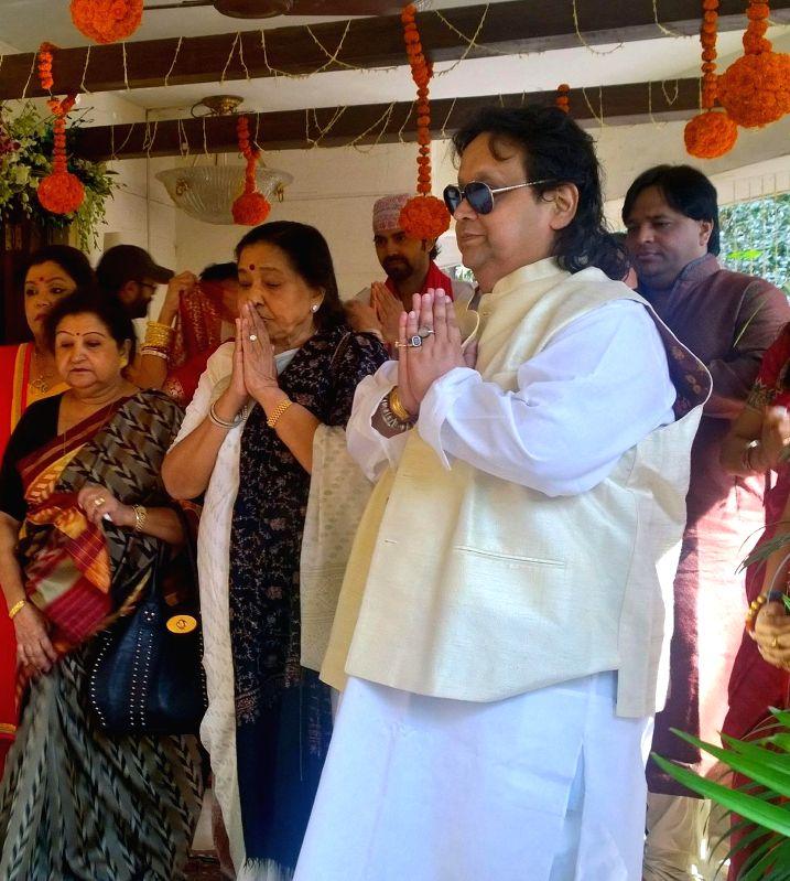 Singer Asha Bhosle and Bappi Lahiri at Bappi Lahiri`s Saraswati Puja at his residence in Mumbai on Jan 25, 2015. - Asha Bhosle