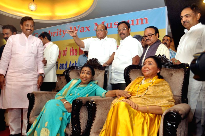 Singer Asha Bhosle sits besides her wax statue at Wankhede Stadium in Mumbai, on April 15, 2015. Also seen singer Asha Bhosle
