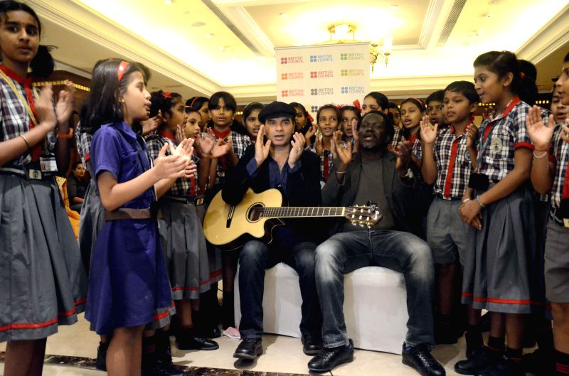 Singer Mohit Chauhan and Senegalese musician Metzo Djatah perform with children during a music programme organised by the British Council in Mumbai on March 18, 2015.
