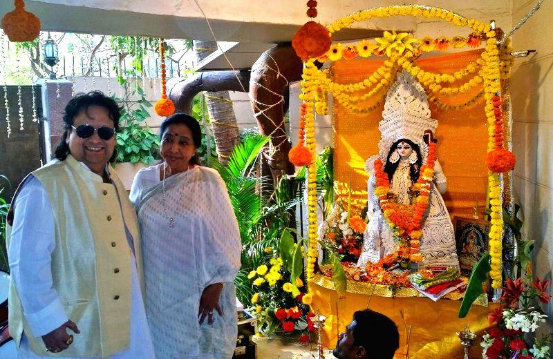 Singers Bappi Lahiri and Asha Bhosle at Bappi Lahiri`s Saraswati Puja at his residence in Mumbai on Jan 25, 2015. - Asha Bhosle