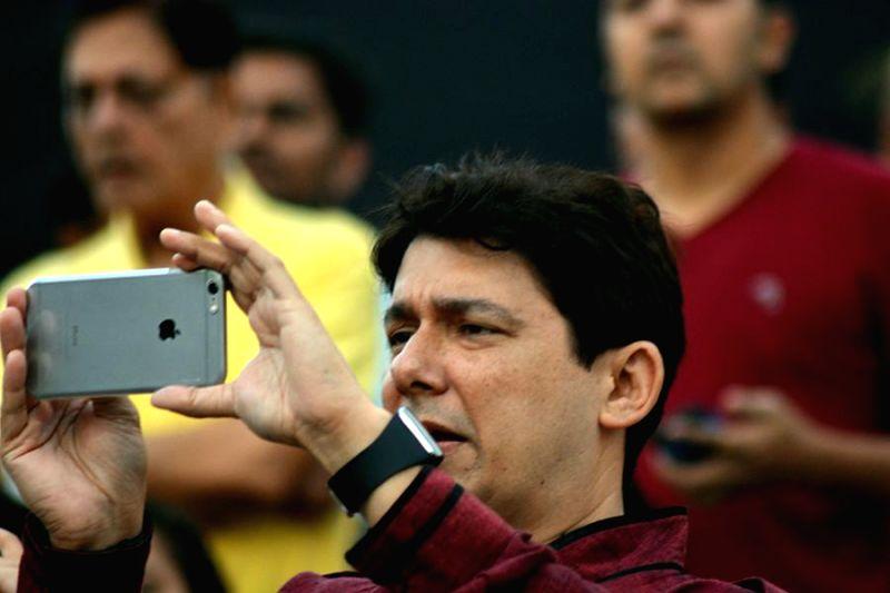 Sriram nene clicking his son's performance during the inauguration of Kala Ghoda festival in Mumbai on Feb. 7, 2015.
