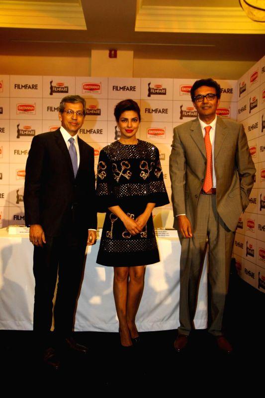 Tarun Rai, CEO, Worldwide Media, Bollywood actor Priyanka Chopra and Varun Berry, MD, Britannia Industries Ltd during the announcement of the 60th Britannia Filmfare awards in Mumbai on ... - Priyanka Chopra and Tarun Rai