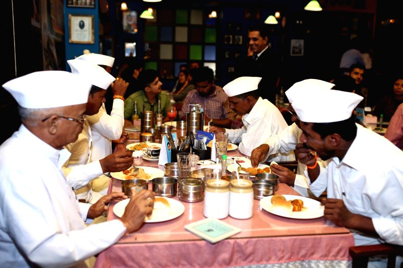 Mumbai: The Dabbawalas and bloggers enjoying the meals served in dabbas at restaurant chain SodaBottleOpenerWala's outlet.