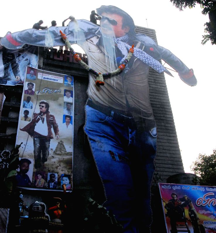 The fans of actor Rajinikanth pour milk on a poster his as the celebrate his birthday in Mumbai on Dec 12, 2014.
