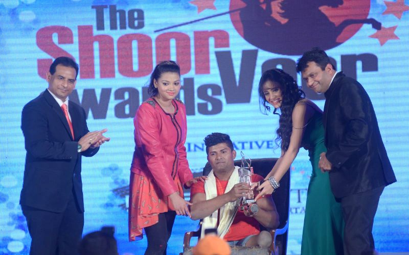 Vinod Thakur receiving award from Shweta Khanduri and Aneel Murarka during the `Shoorveer Awards` in Mumbai on March 15, 2015.