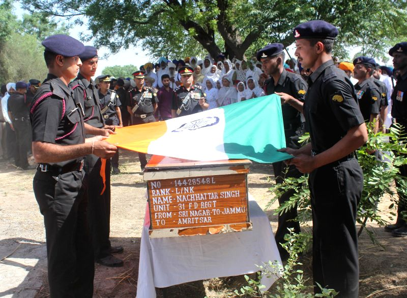Army soldiers pay respect to L/Naik Nachhattar Singh at his village Munda Pind in Amritsar district on May 2, 2015. Nachhattar Singh was killed in a terrorist attack in Srinagar.