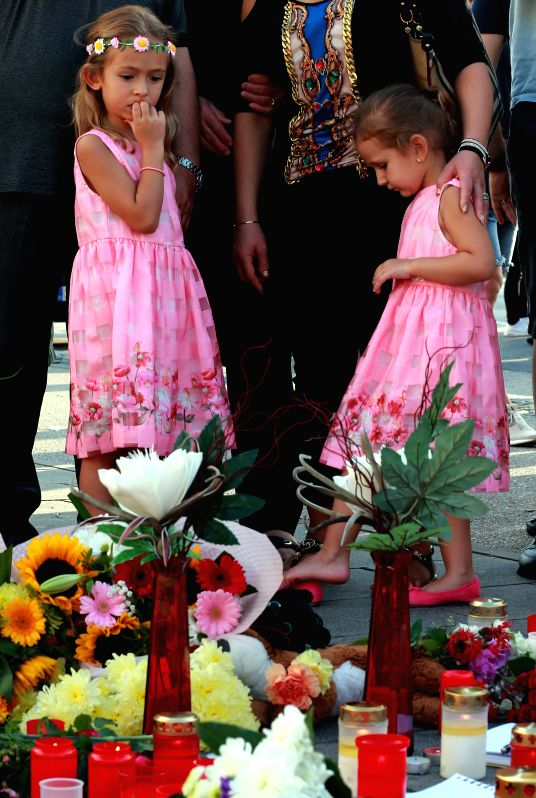 MUNICH (GERMANY), July 25, 2016 People light candles and offer flowers to mourn the Friday shootout victims in front of the Olympia shopping mall in Munich, Germany, on July 24, 2016.  ...