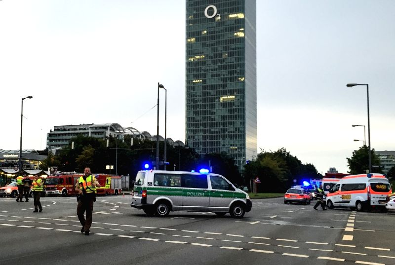 MUNICH, July 22, 2016 - Photo taken by a mobile device shows police standing guard near the site of the shootout in Munich, Germany, on July 22, 2016. At least six people were killed in a shootout in ...