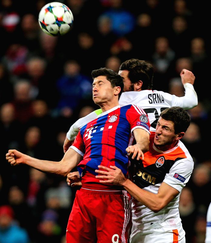 Bayern Munich's Robert Lewandowski (L) vies for the ball during the UEFA Champions League Round of 16 second leg match against Shakhtar Donetsk in Munich, Germany, ...