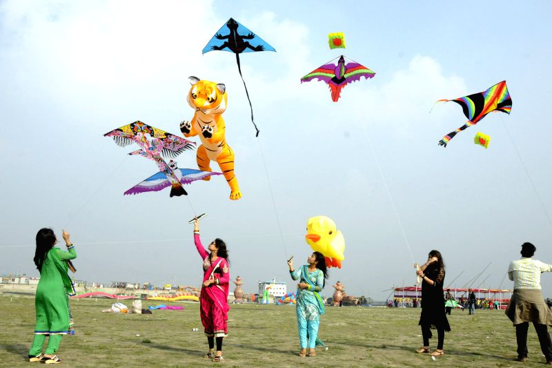 Bangladeshi teenagers fly kites during the national kite festival at the bank of Padma River in Munshiganj district, some 37 km from capital Dhaka, Bangladesh, ..