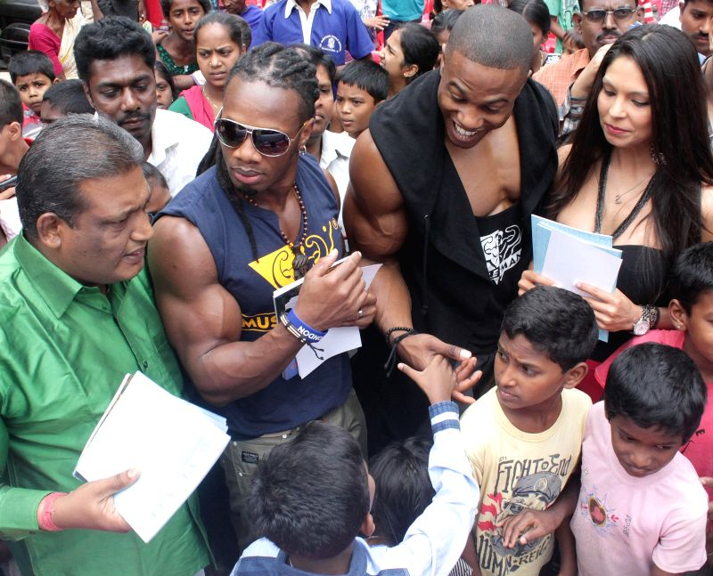 Muscle mania World Pro Champion-2013 Ulisses Jr, Musclemania Europe Champion-2013 Simeon Panda and Model America Champion Jessica Vasqeuz distribute note books to under privileged children during a .. - America Champion Jessica Vasqeuz