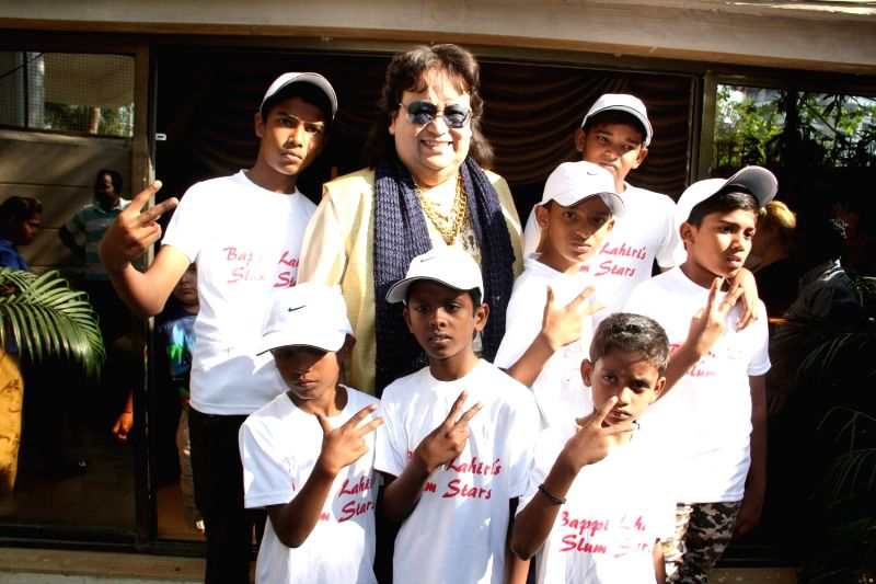 Music director Bappi Lahiri with singers from the slums of Mumbai, where he has shortlisted 6 of them and trained and made them record an album Slumstars in Mumbai, on Feb 9, 2015.