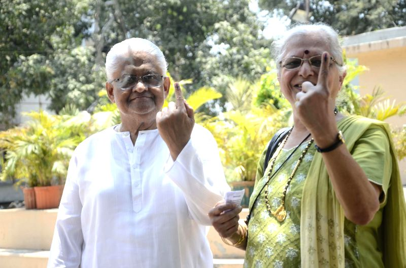 Music director Pyarelal and his wife show their fore fingers marked with phosphorous ink after casting their votes at a polling booth during the sixth phase of 2014 Lok Sabha Polls in Mumbai on April