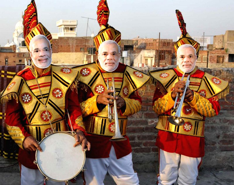 Musicians wearing masks of BJP Prime Ministerial candidate and Gujarat Chief Minister Narendra Modi rehearse ahead of declaration of 2014 Lok Sabha Election results in Amritsar on May 15, 2014. - Narendra Modi