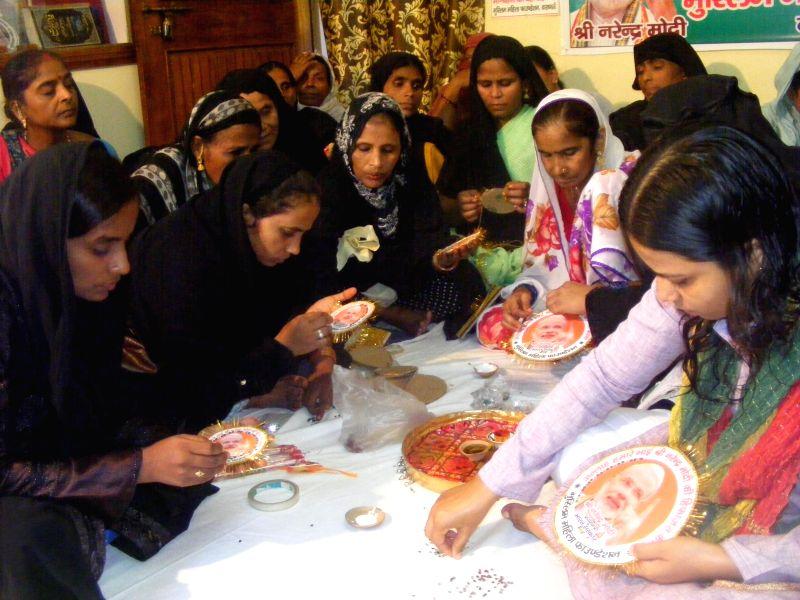 Muslim women make Rakhis with picture of Prime Minister Narendra Modi in Varanasi on Aug 7, 2014.