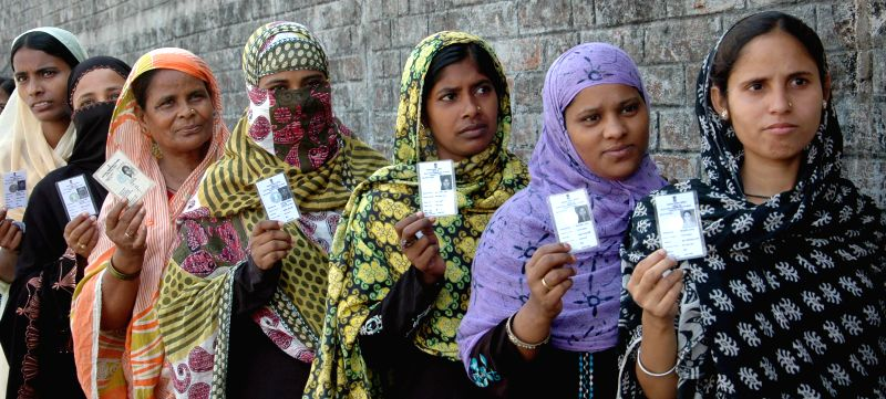 Muslim women show their voter's identity card as they queue-up to cast their vote at a polling booth during the seventh phase of 2014 Lok Sabha Polls in Sreerampur of West Bengal on April 30, 2014.