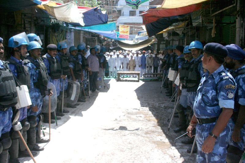 Muslims offer prayers on occasion of Eid-ul-Fitr as police personnel stands guard in Varanasi on July 29, 2014.