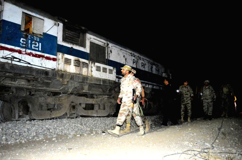 Pakistani soldiers inspect the train at the blast site in southwest Pakistan's Mustang on Nov. 20, 2014. At least 12 people were injured when a passenger train derailed after a blast in ...