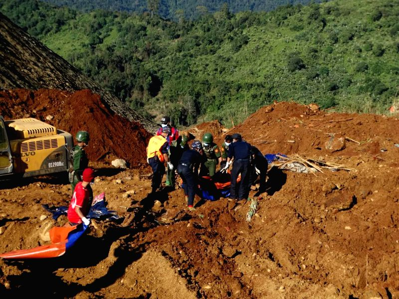 Myanmar soldiers and rescuers carry the bodies of miners in Hpakant, Myanmar's northernmost Kachin state, Nov. 22, 2015. At least 94 bodies have been recovered on ...