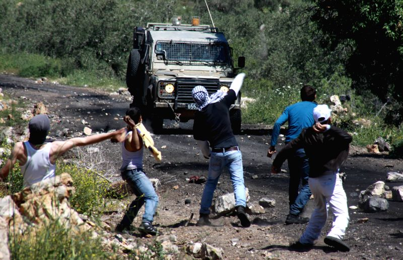 Palestinian protesters hurl stones at Israeli soldiers during a protest against the expanding of Jewish settlements in Kufr Qadoom village near the West Bank city ..