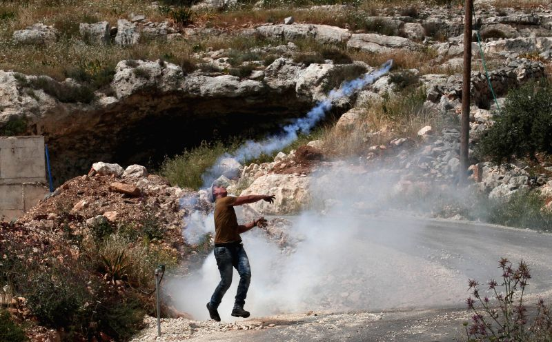 NABLUS, April 13, 2018 - A Palestinian protester uses a slingshot to hurl stones at Israeli soldiers during clashes after a protest against the expanding of Jewish settlements in Kufr Qadoom village ...