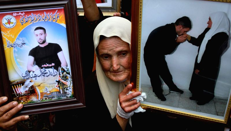 A Palestinian woman holds a picture of her relative in Israeli jails as she takes part in the commemoration marking Palestinian Prisoner Day, which is a solidarity .
