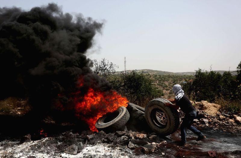 NABLUS, April 20, 2018 - A Palestinian protester burns tires after a protest against the expanding of Jewish settlements in Kufr Qadoom village near the West Bank city of Nablus, on April 20, 2018.