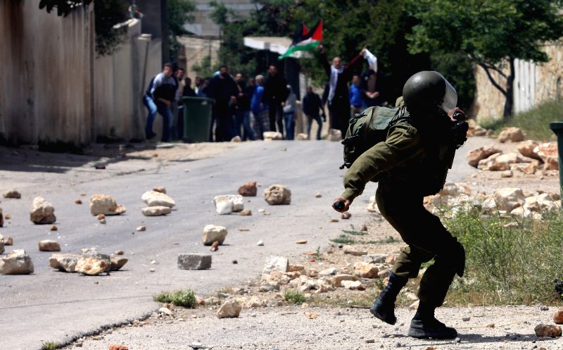 An Israeli soldier shots a tear-gas canister at Palestinian protesters during a protest against the expanding of Jewish settlements in Kufr Qadoom village near the ...