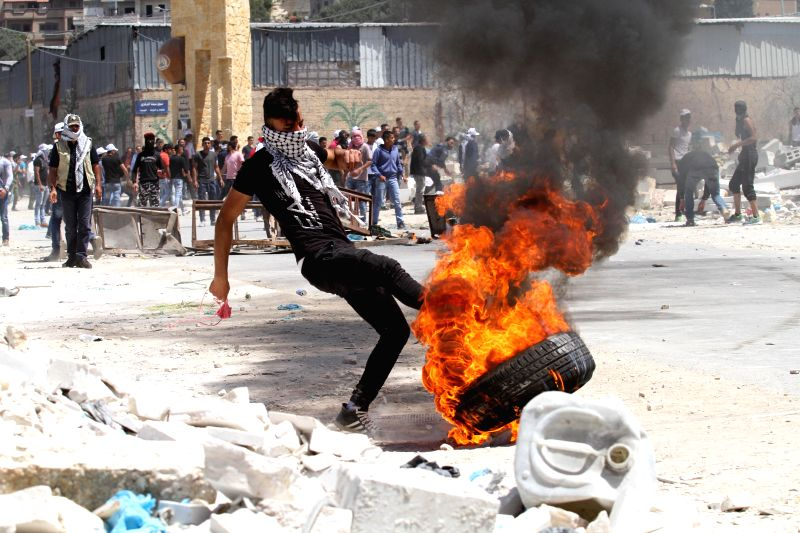 NABLUS, April 28, 2017 - A Palestinian protester burns tires during clashes with Israeli soldiers in a protest in support of Palestinian prisoners on hunger strike in Israeli jails, in Beita village ...