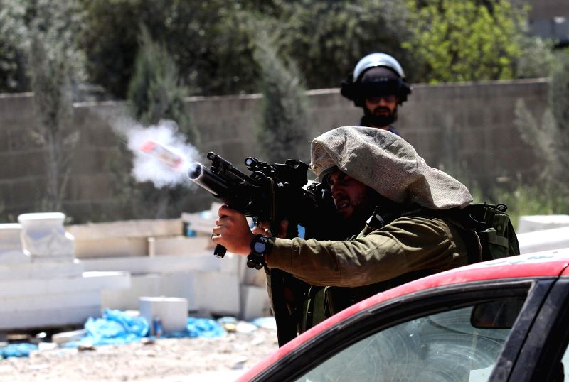 NABLUS, April 28, 2017 - An Israeli soldier shots fire at Palestinian protesters during clashes with Israeli soldiers in a protest in support of Palestinian prisoners on hunger strike in Israeli ...