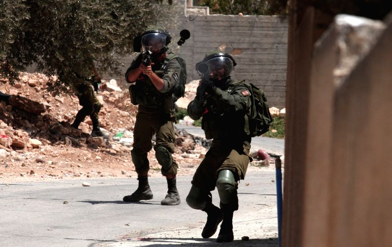 NABLUS, Aug. 11, 2018 - Israeli soldiers aim their weapons at Palestinian protesters during clashes after a protest against the expanding of Jewish settlements in Kufr Qadoom village near the West ...