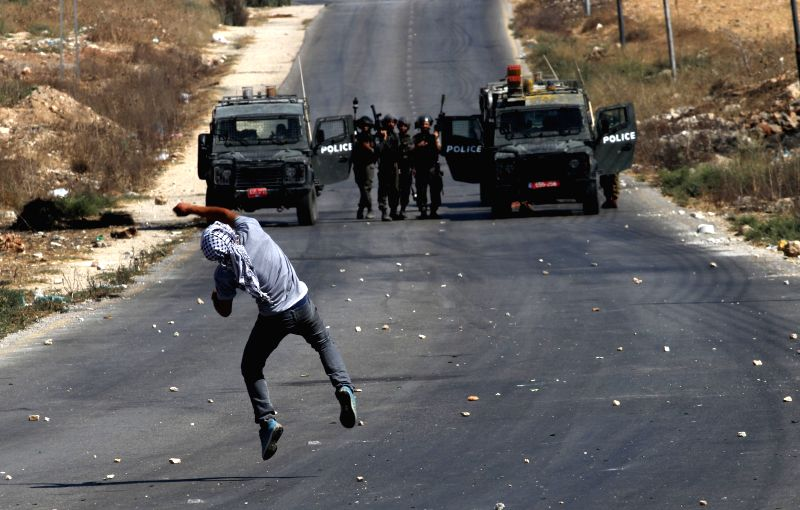 A Palestinian protester throws stones at Israeli soldiers during clashes following a demonstration against the Israeli offensive in the West Bank village of Beit ...