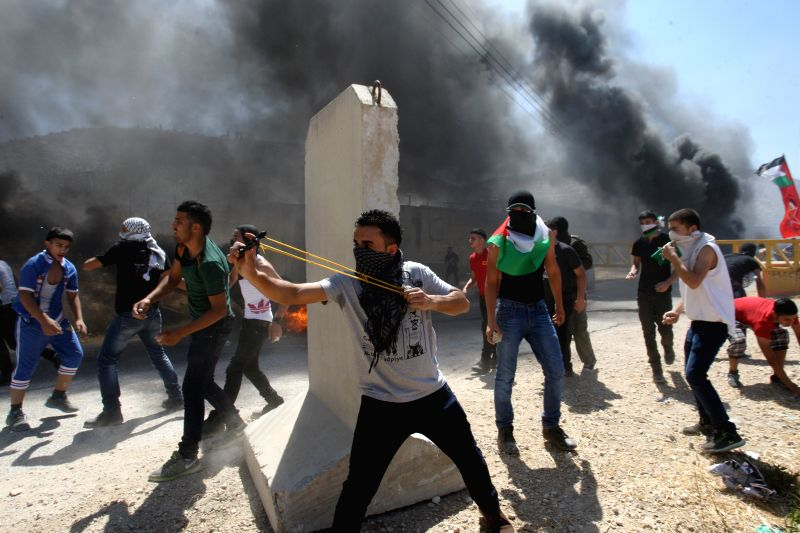 Palestinian protestors hurl stones at Israeli soldiers during clashes following a demonstration against the Israeli offensive in Gaza, at the Beit Fourik checkpoint ..