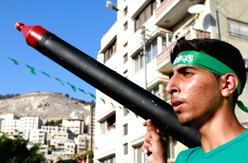 A Palestinian supporter of the Hamas Islamist movement holds a mock rocket as he takes part in a rally following the Friday prayers, on Aug. 29, 2014 in the West ..