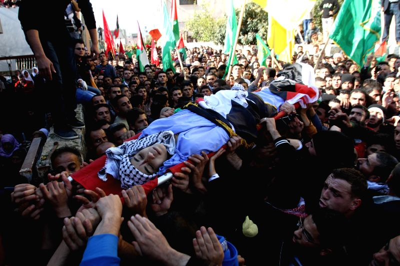 Mourners carry the body of 17-year-old Palestinian teenager Omam Dwekat, who was shot dead by Israeli troops the day before, during his funeral in the West Bank ...
