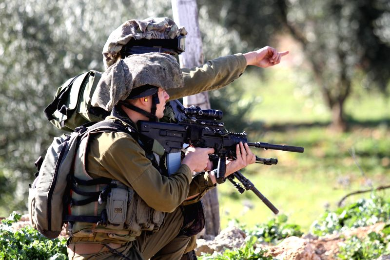 Israeli soldiers take positions during clashes with Palestinian protesters near the Jewish settlement of Majdolim, close to Qusra village, south of the West Bank city