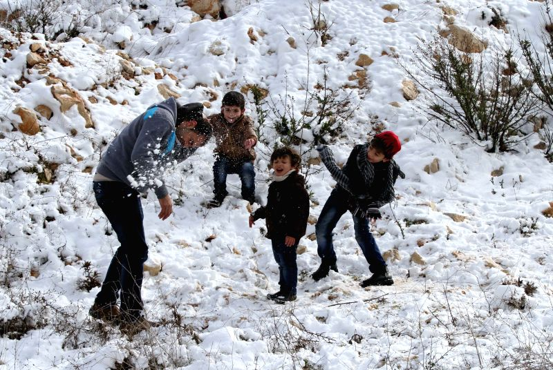 Palestinians play with snow in the West Bank city of Nablus, Jan. 10, 2015.