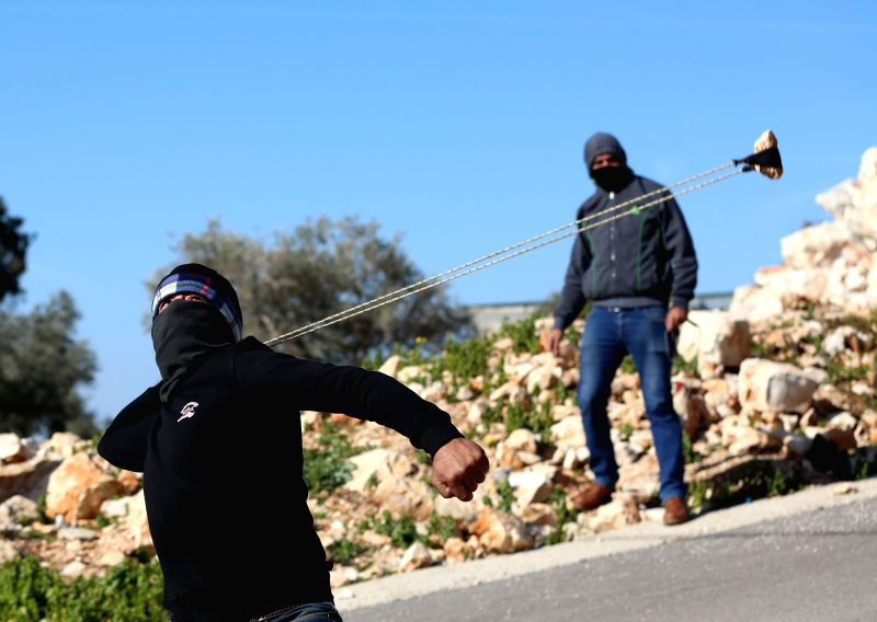 NABLUS, Jan. 11, 2019 - A Palestinian protester uses a slingshot to hurl stones at Israeli soldiers during clashes after a protest against the expanding of Jewish settlements in Kufr Qadoom village ...