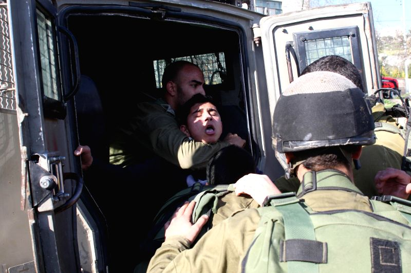 Israeli soldiers detain a Palestinian protester during a protest against the Israeli check points at the Israeli Hawara checkpoint near the West Bank city of Nablus, .