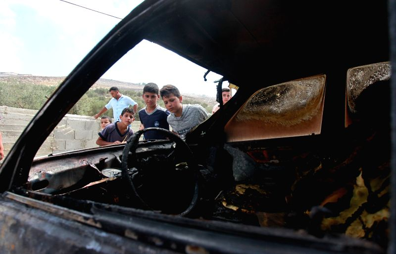 NABLUS, July 13, 2018 - Palestinian boys inspect a burned car after Jewish settlers set them on fire, in Urif village near the West Bank city of Nablus, on July 13, 2018. Earlier on Tuesday, ...