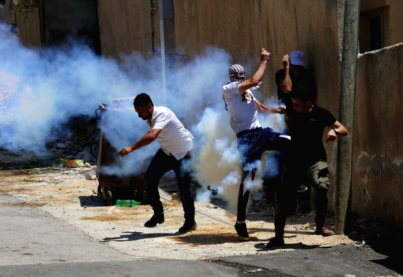 NABLUS, July 27, 2018 - Palestinian protesters run to take cover from tear gas canisters fired by Israeli soldiers during clashes after a protest against the expanding of Jewish settlements at Kufr ...