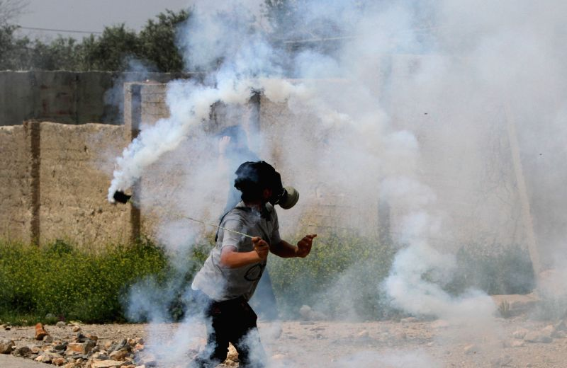 A Palestinian protester hurls back a tear-gas canister shot by Israeli soldiers during a protest against the expanding of Jewish settlements in Kufr Qadoom village ...