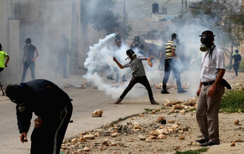 Palestinian protesters hurl back tear-gas canisters shot by Israeli soldiers during a protest against the expanding of Jewish settlements in Kufr Qadoom village near ...